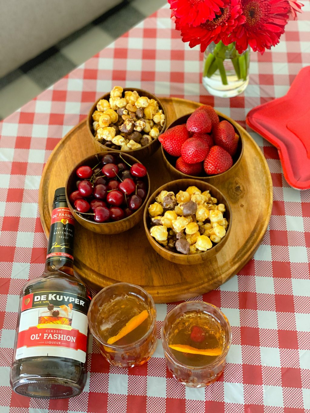 old fashioned liqueur and drinks in glasses on top of red and white checked tablecloth next to wooden tray topped with wooden bowls filled with strawberries, cherries and popcorn