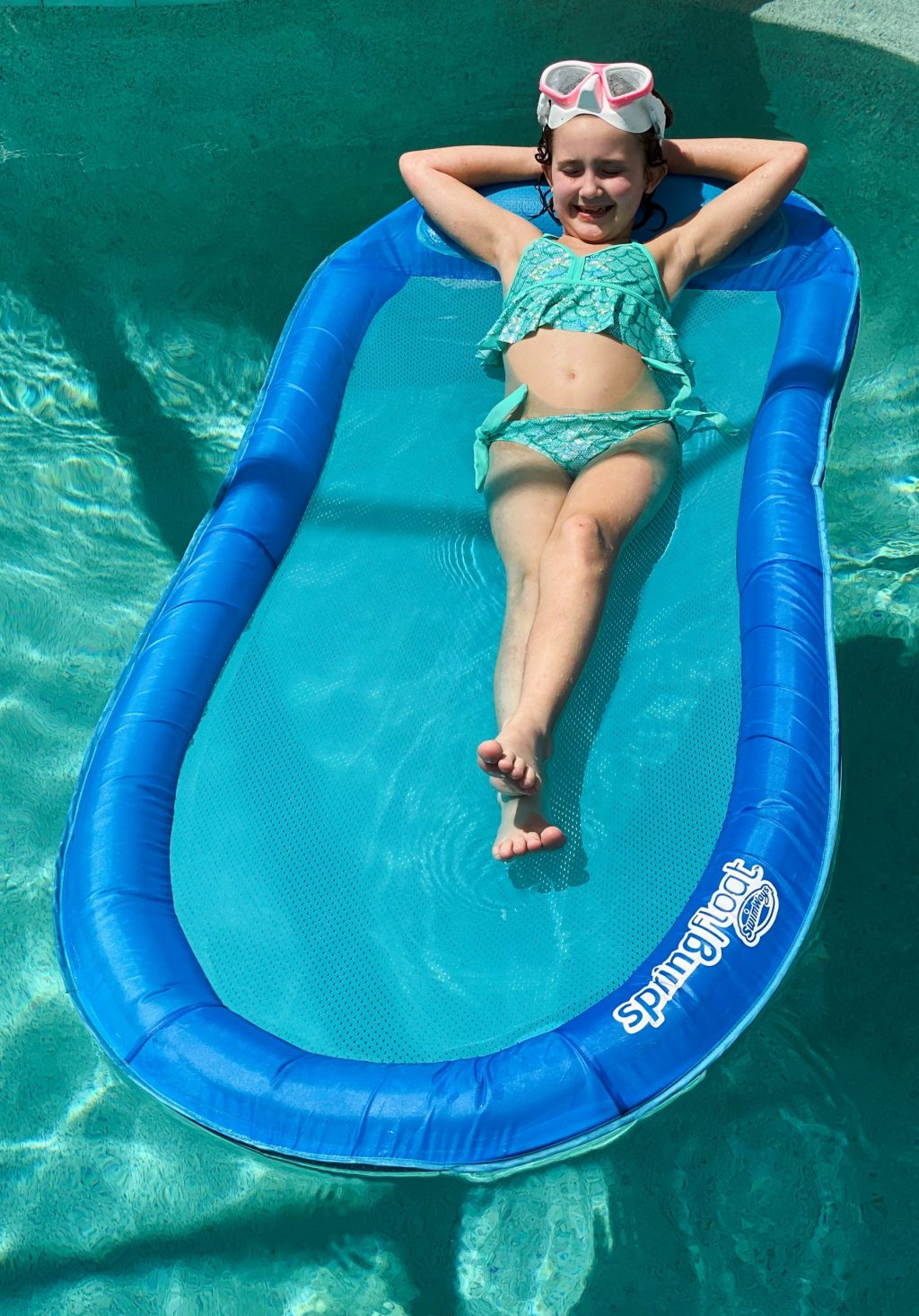little girl in green swimsuit floating on blue spring float in pool