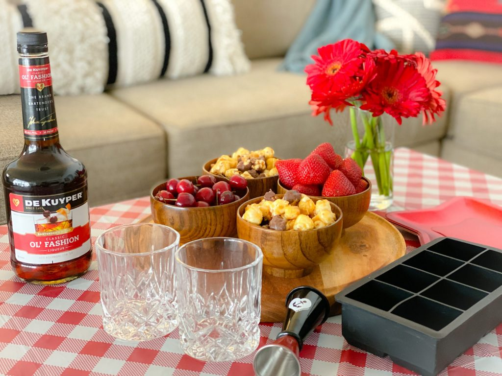 glasses, ice tray, wooden tray with wooden bowls of cherries, popcorn and strawberries on top of red and white checked tablecloth in front of glass filled with red daises