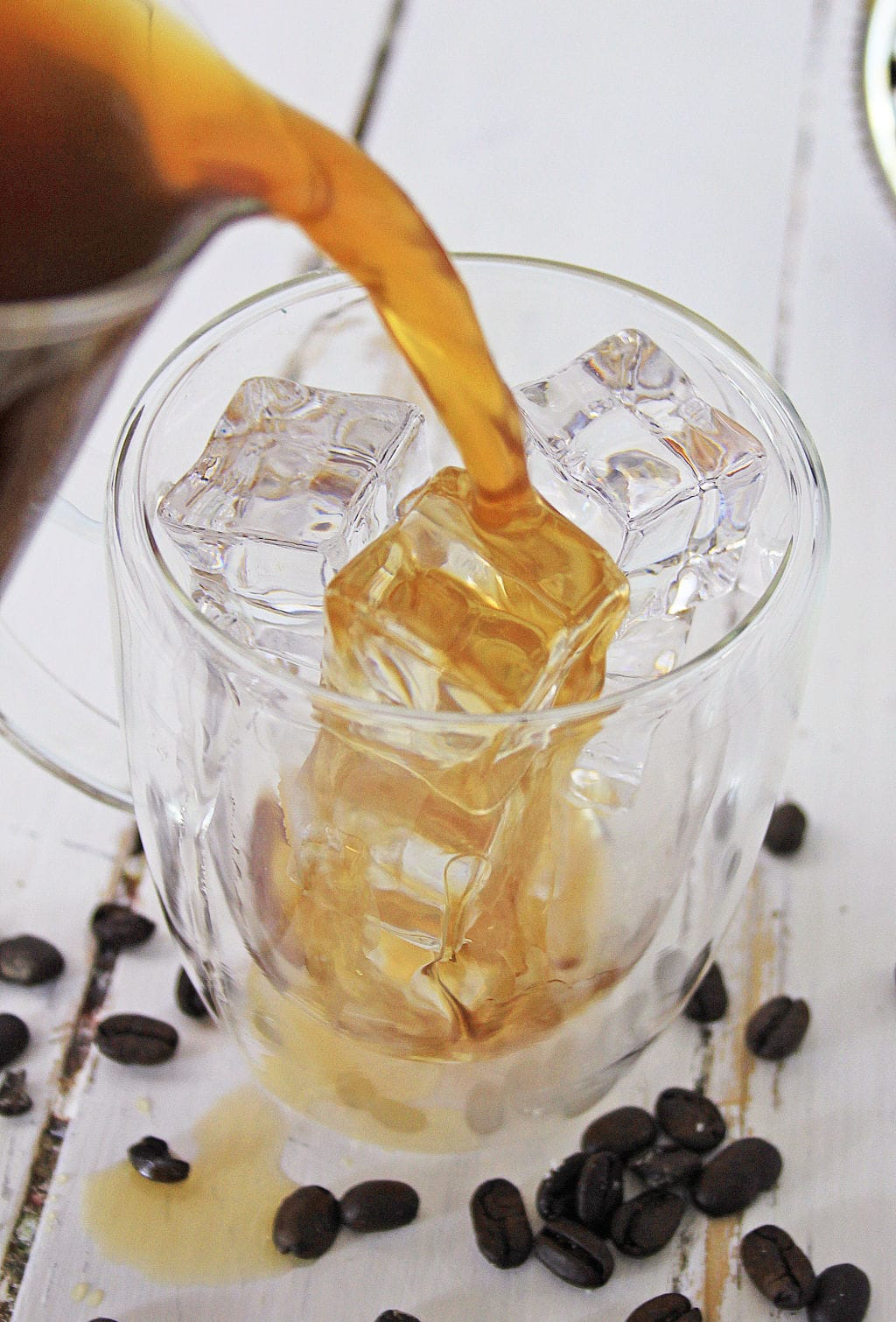 pouring coffee over ice in clear glass mug on top of white wood table with coffee bans scattered on it
