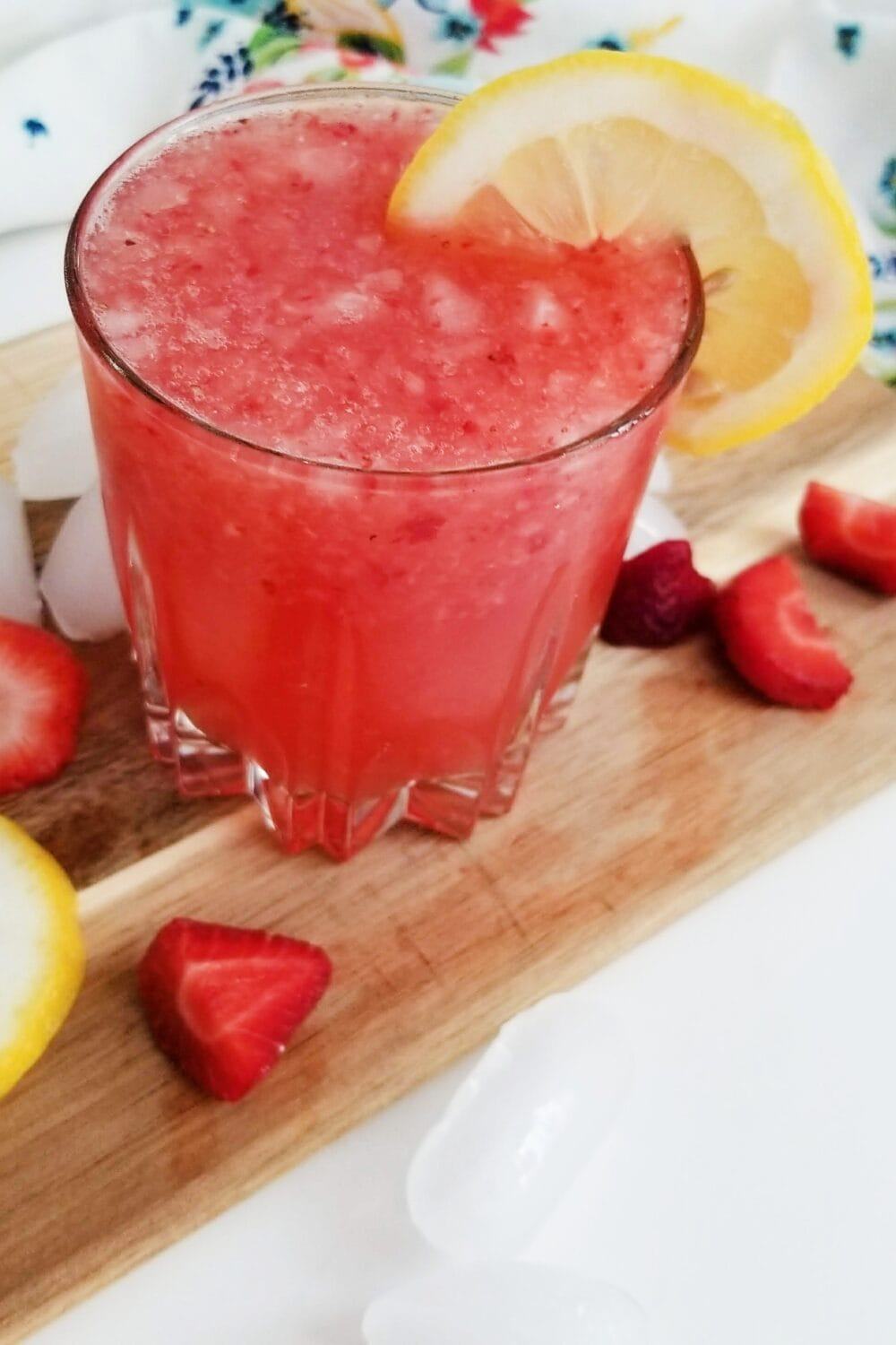 red frozen drink with lemonade slice garnish in clear glass on top of wood cutting board with strawberries and lemon slices scattered on it and white floral napkin in the background