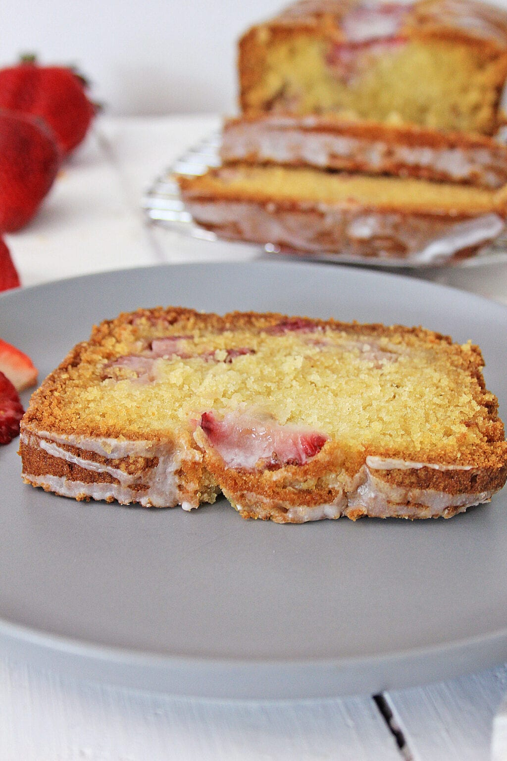 slice of strawberry bread on gray plate in front of sliced loaf of strawberry bread and strawberries on white wooden table