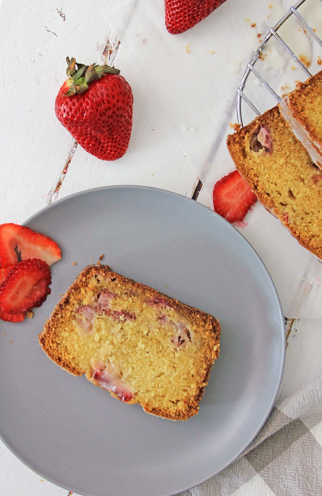 slice of strawberry bread on gray plate next to strawberry bread loaf and strawberries on white wooden table