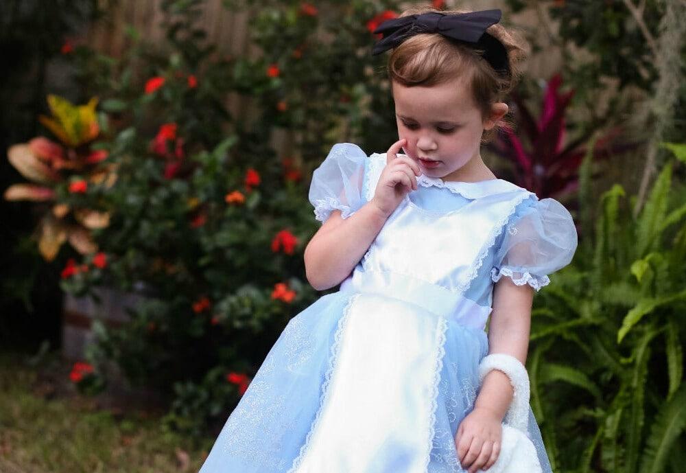 little girl standing in yard wearing blue alice in wonderland costume