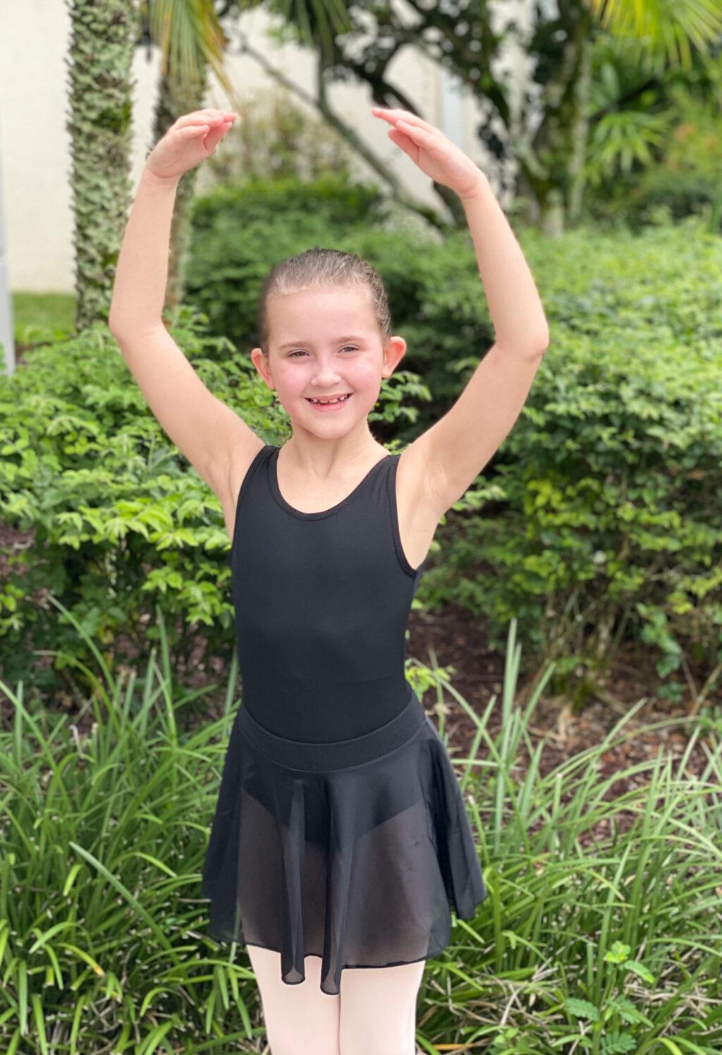 little girl in black leotard and black skirt in ballet pose