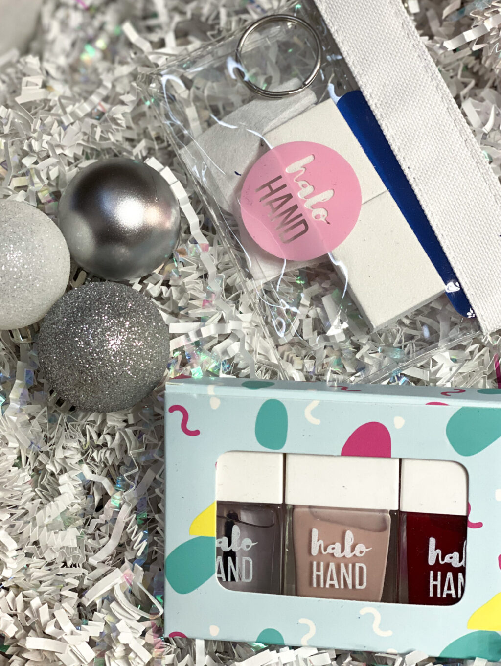 pink and red nail polish and mainicure kit next to silver ball ornaments