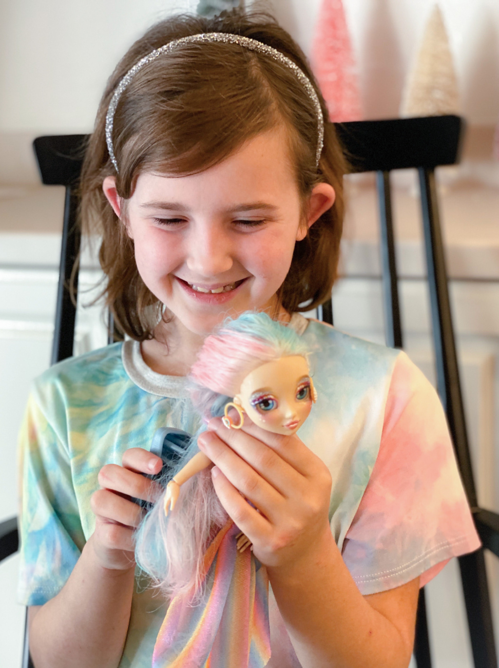 little girl in pastel tie dye outfit brushing pink and blue doll hair