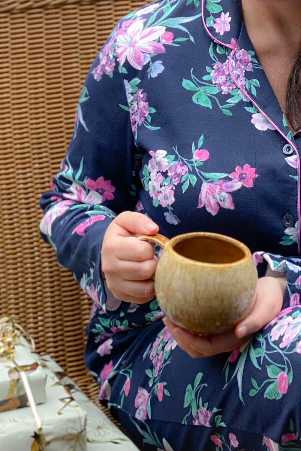 woman in navy and pink floral pajams holding brown coffee mug next to ivory and gold wrapped packages