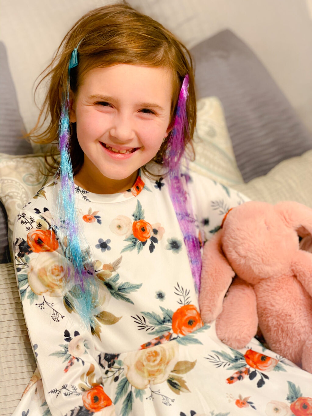 little girl in white floral dress wearing turquoise and purple hair extensions holding pink plush rabbit