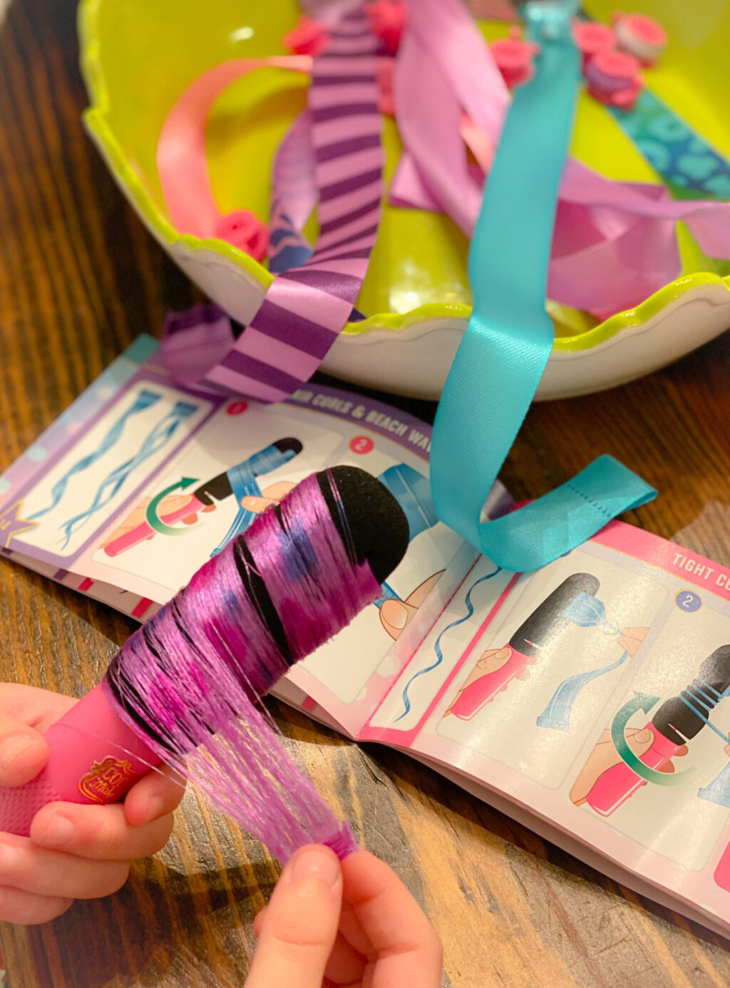 curling a purple hair extension over wood table with instruction booklet and green bowl filled with pink, purple and turquoise hair extensions
