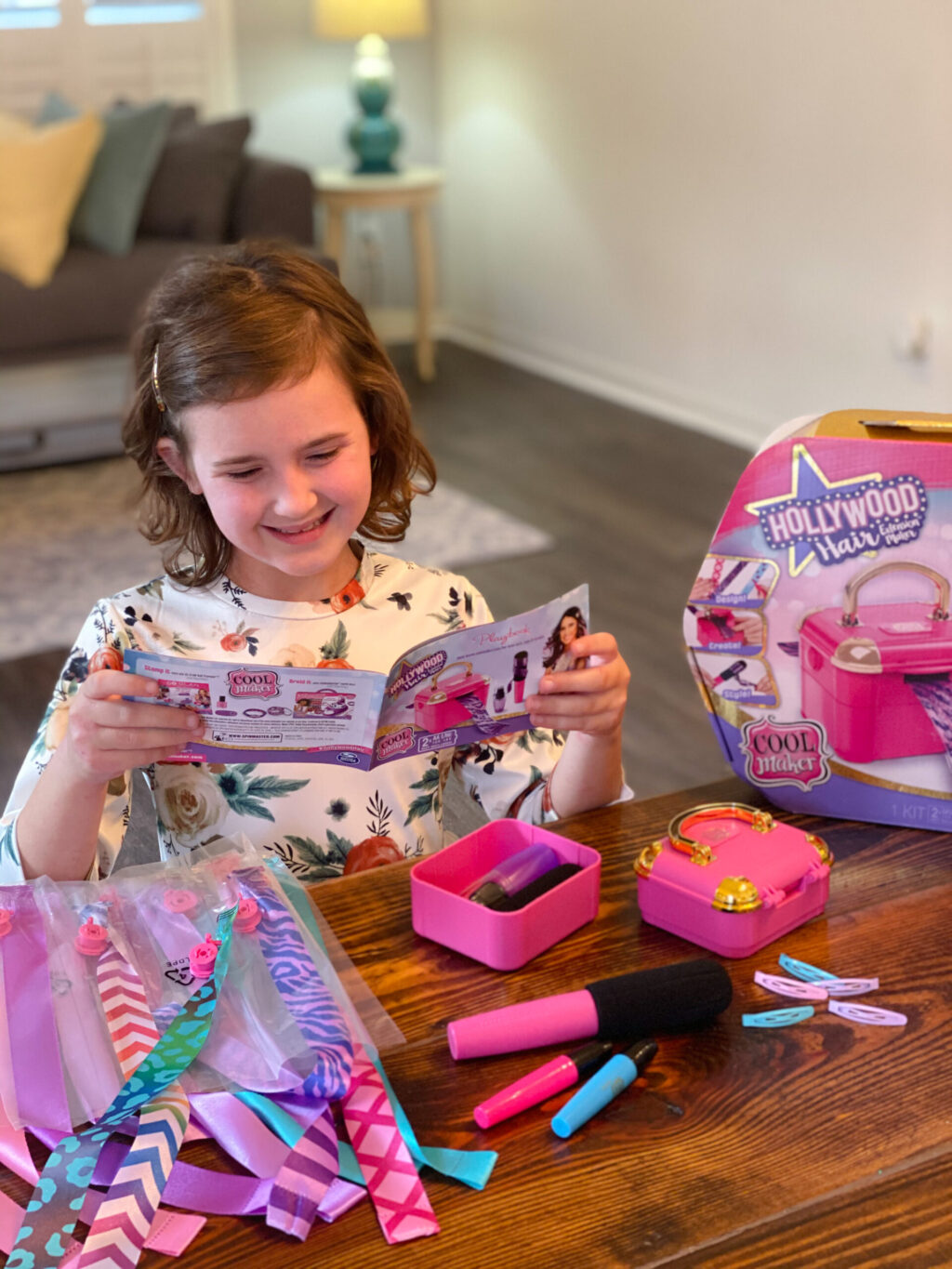 little girl looking at instruction booklet while sitting at brown wooden table with pink and purple hair extension kit supplies
