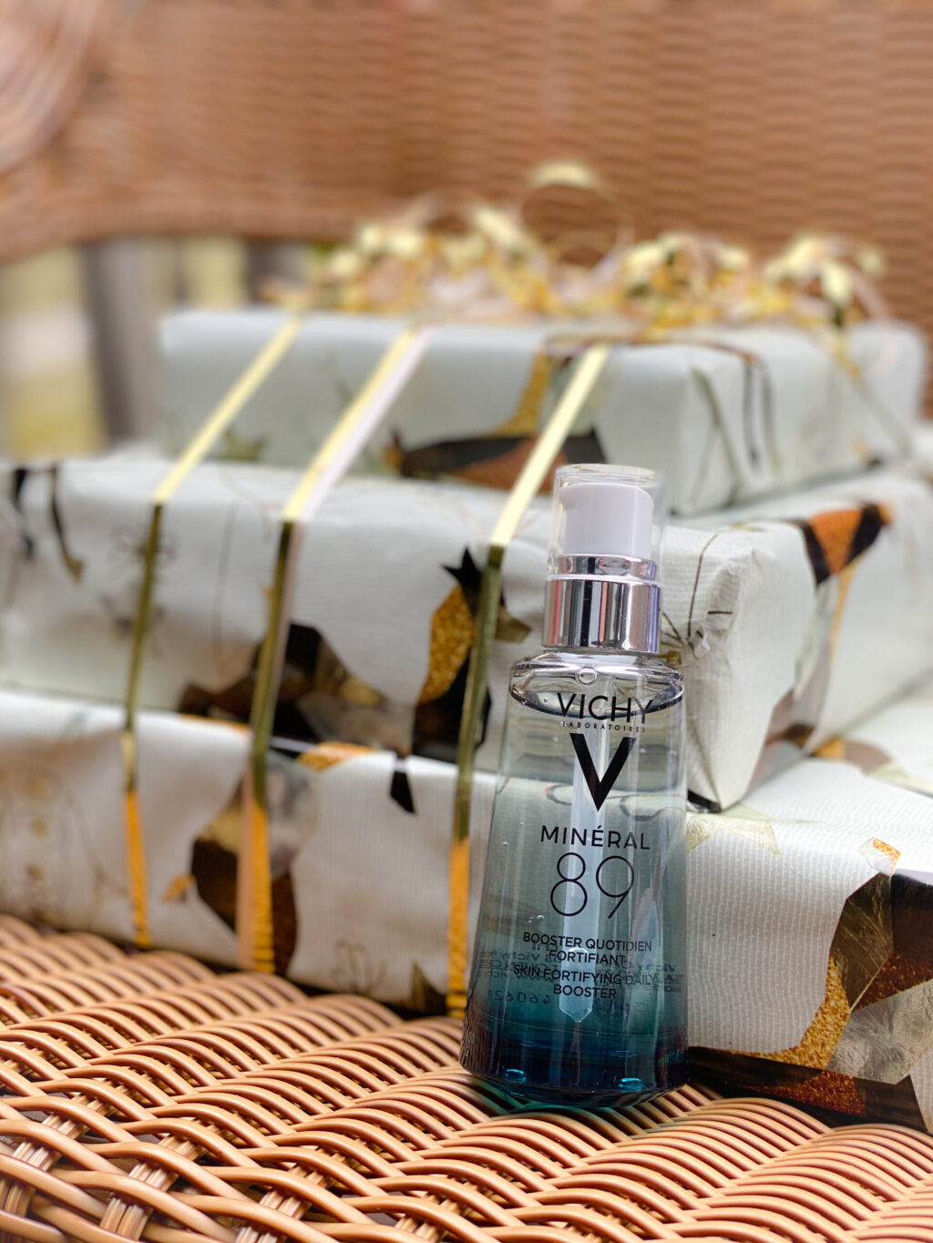 vichy mineal. 89 serum in blue bottle next to gold and ivory wrapped packages