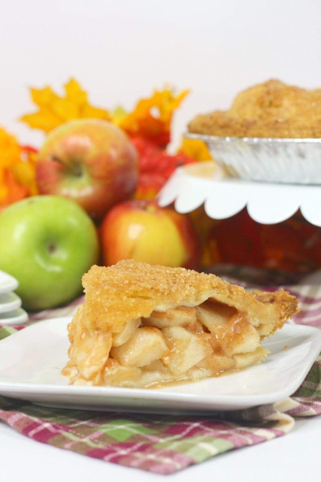 slice of apple pie on a white plate in front of a white cake plate and green and red apples