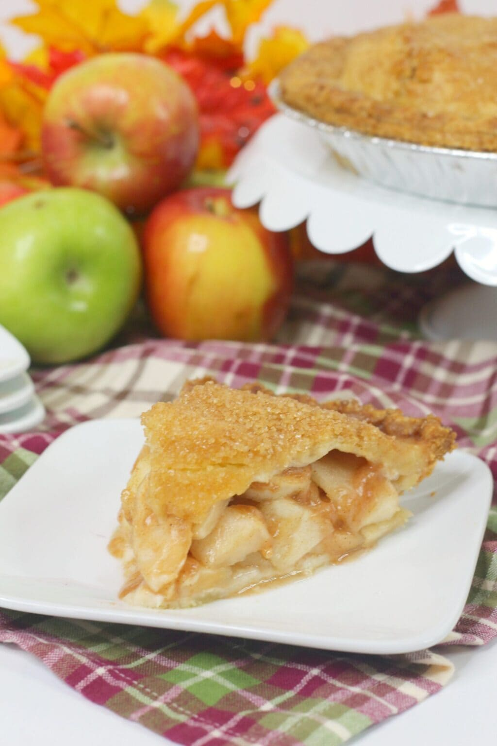 apple pie slice on white plate next to red plaid napkin and red and green apples