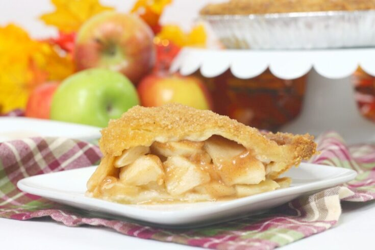 apple pie slice on white plate on red plaid napkin in front of red and green apples