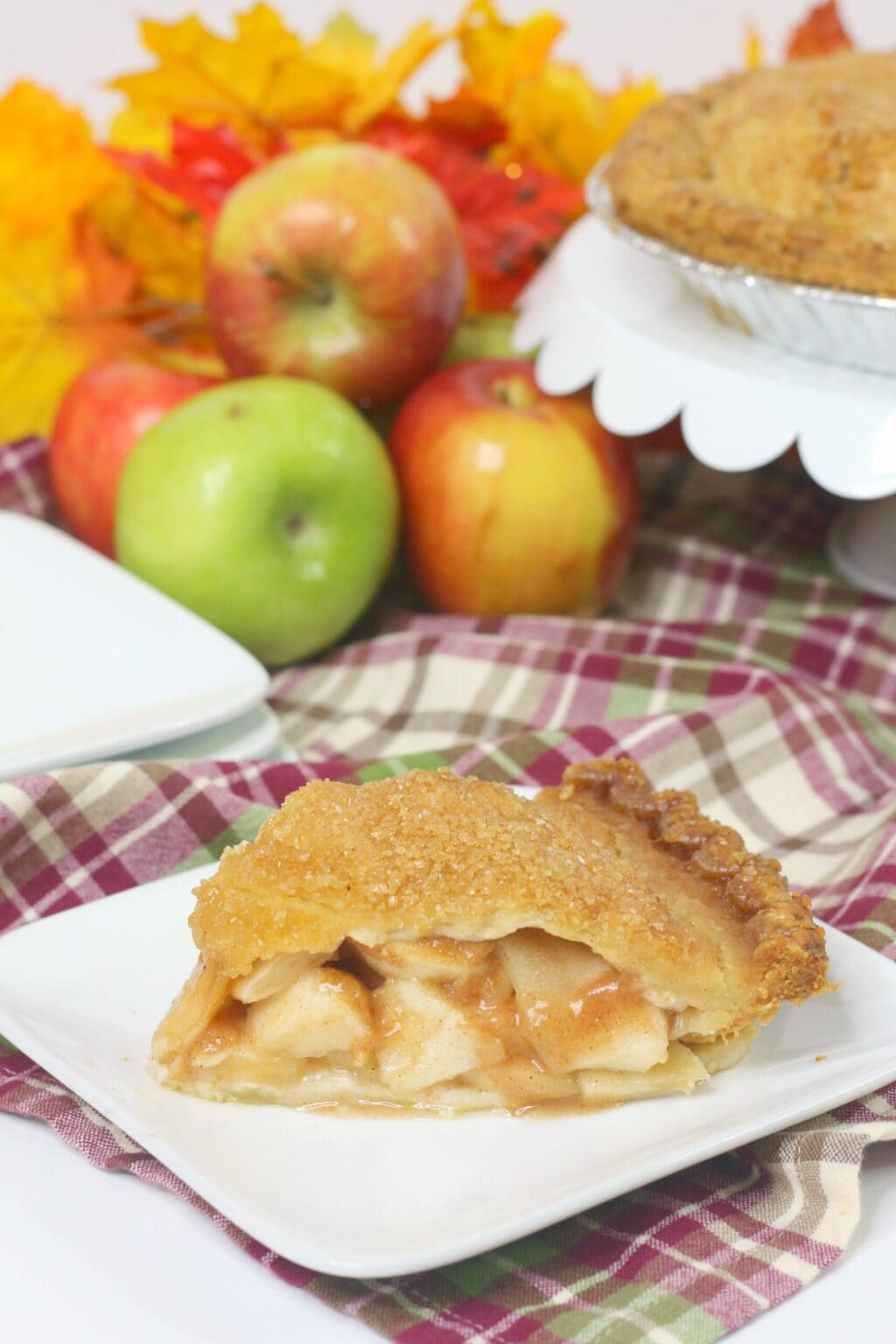 apple pie slice on white plate on top of red plaid napkin next to white cake plate and red and green apples