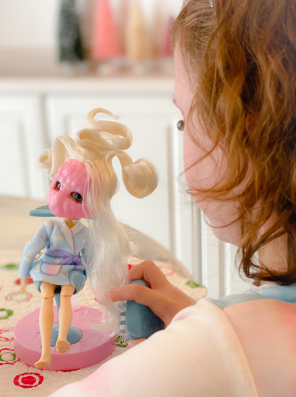 little girl with brown hair brushing blond doll with pink face mask