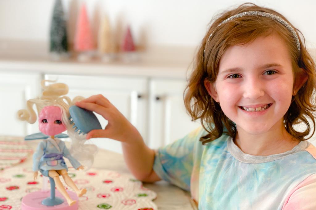 little girl in pastel tie dye shirt brushing blond doll's hair