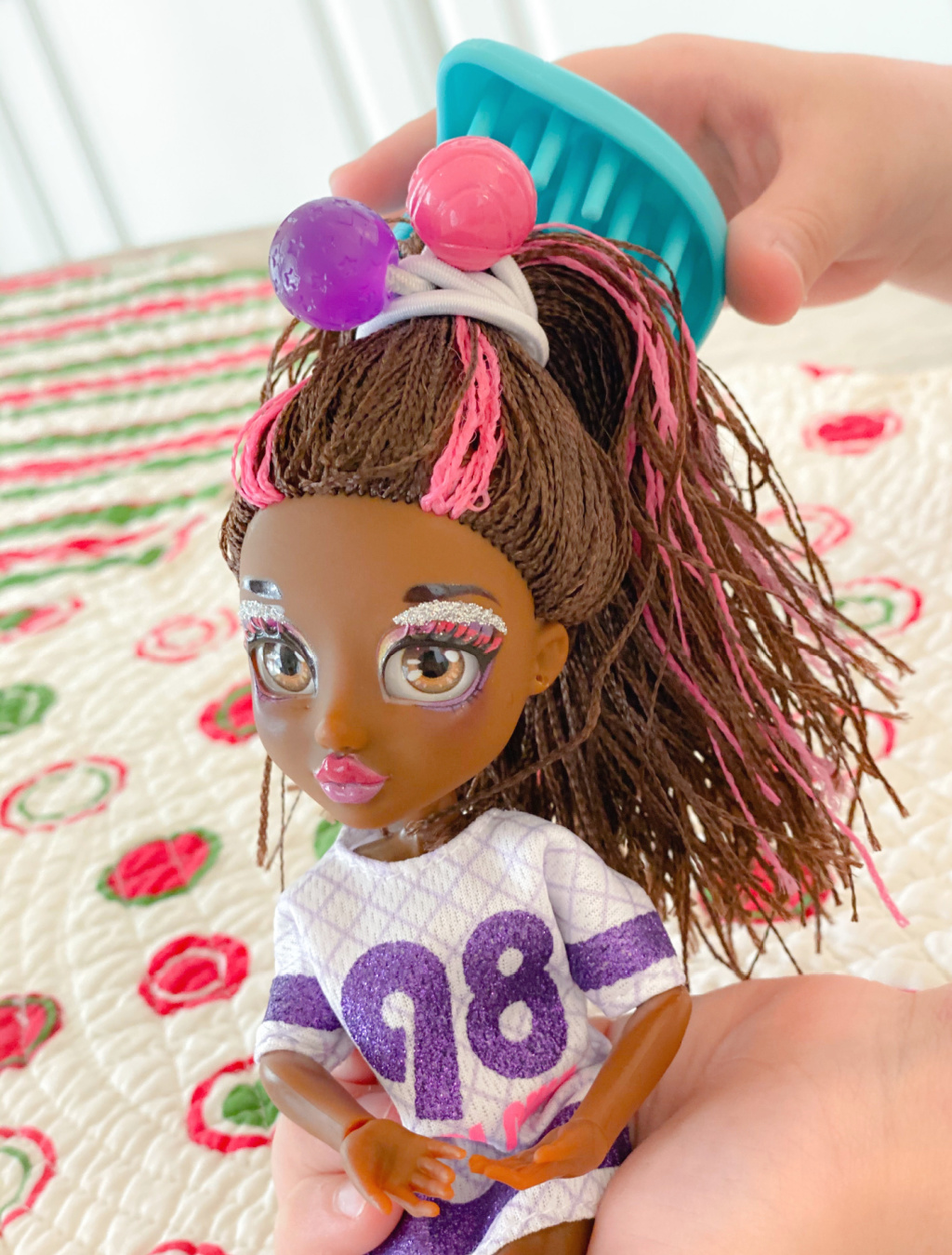 putting brown and pink doll hair in ponytail