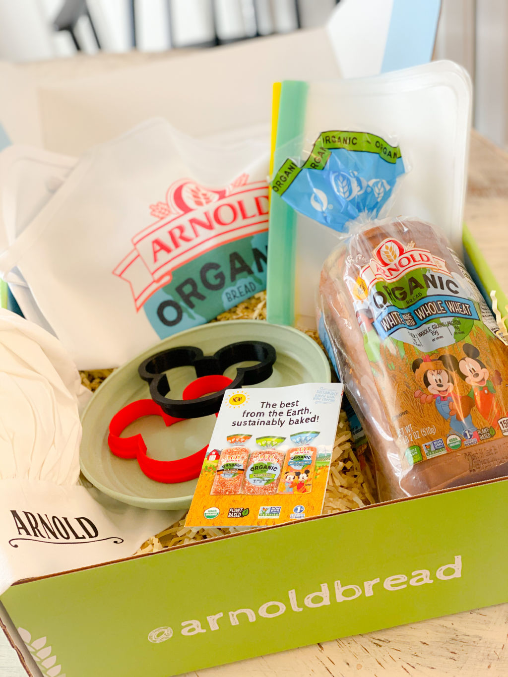 green box filled with arnold's organic bread loaf, white apron, white chef's hat, and red and black mickey mouse cookie cutters