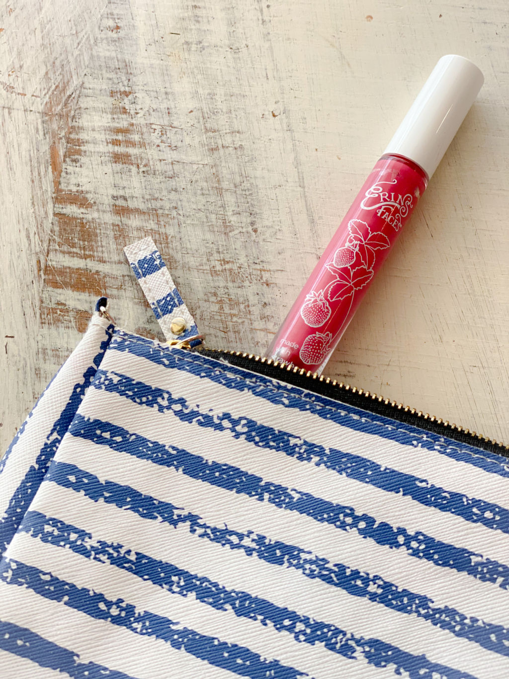 pink lip gloss with white cap peeking out of blue an white striped bag on top of white distressed table