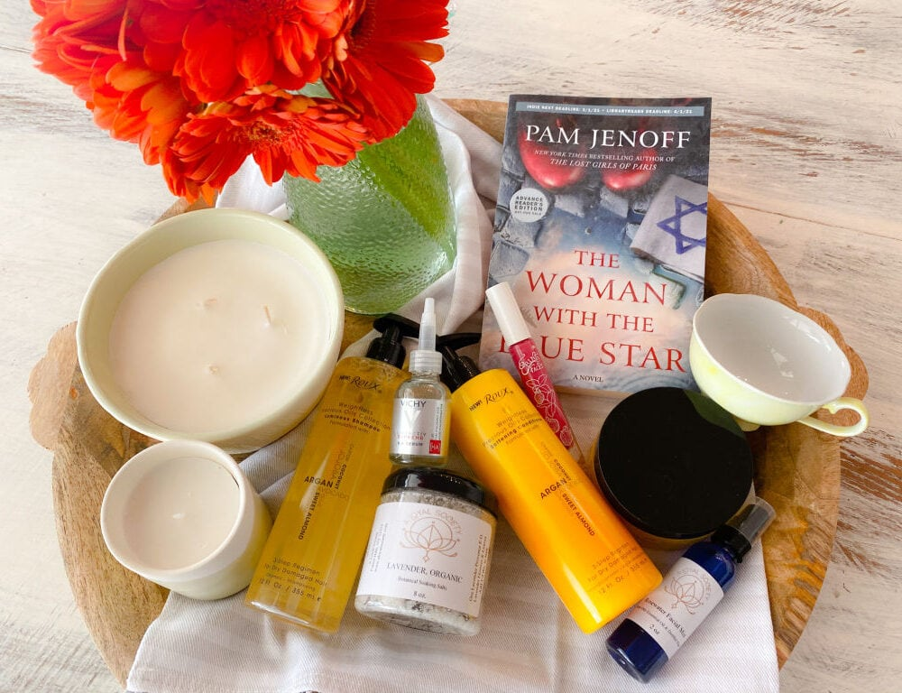 yellow bottles of shampoo and conditioner, clear bottle of facial oil, book with a blue cover, 2 off white round candles, pink lip gloss and a green vase with orange daisies on brown mango wood tray