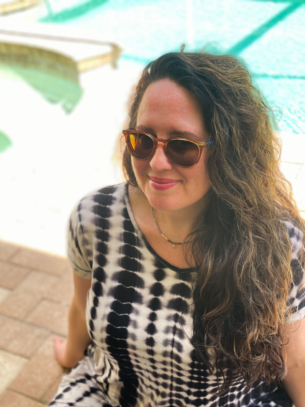 woman with curly brown hair wearing brown sunglasses and black and white tie dye dress in front of a pool