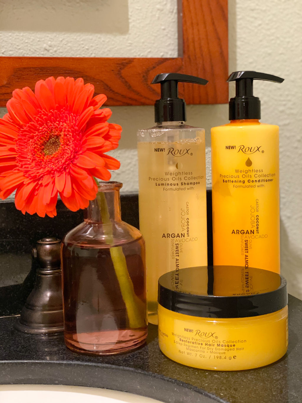 yellow shampoo, conditioner and hair masque bottles with black caps on black counter next to pink vase and orange daisy