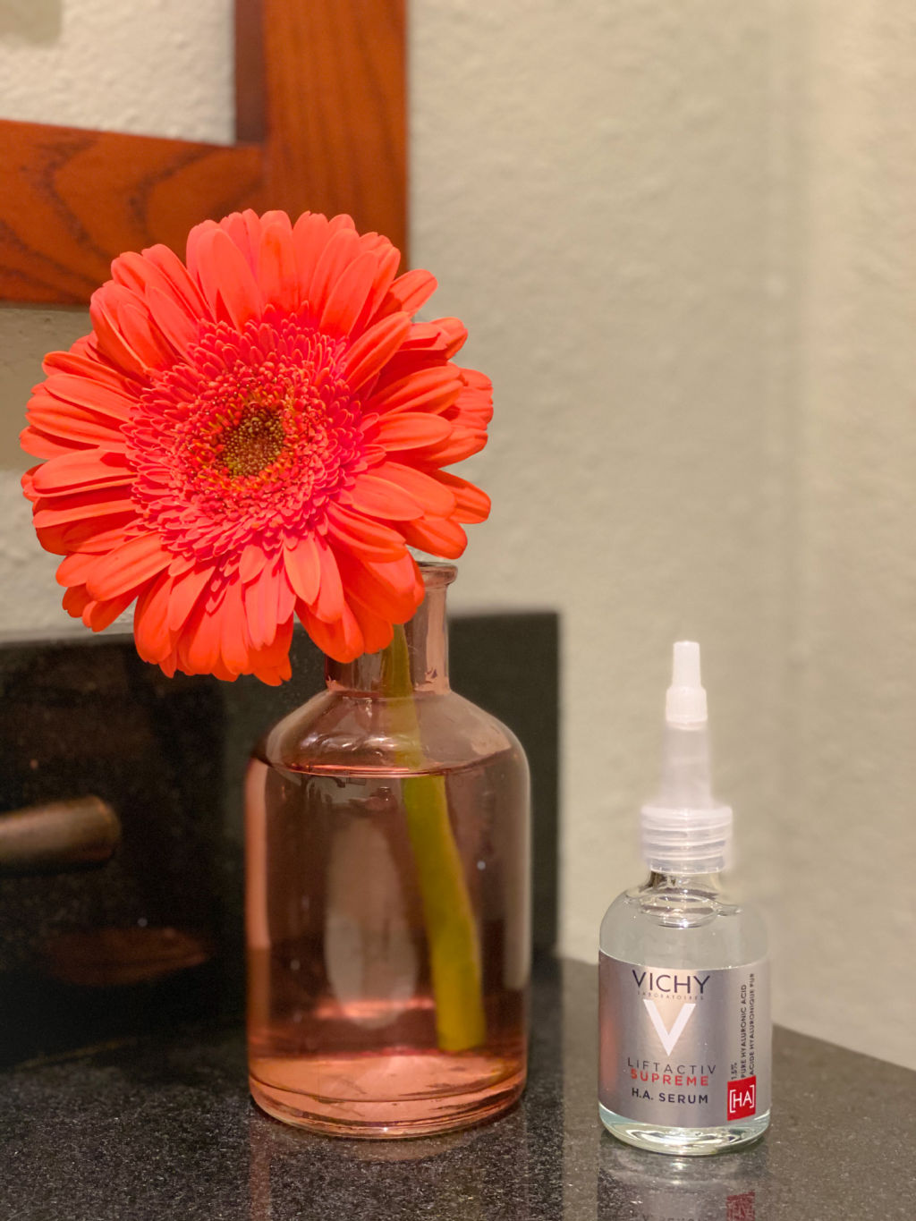 pink vase with orange daisy on black counter next to clear bottle of face serum